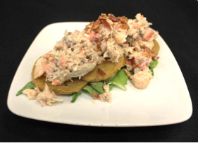 Seafood Salad with Maine Lobster, Shrimp. Crab in a light Tarragon Mayonnaise over Fried Green Tomatoes, topped with bacon bits